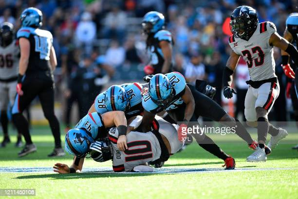 Christian Kuntz, Asantay Brown, and Tenny Adewusi of the Dallas Renegades make a tackle during the XFL game against the New York Guardians at Globe...