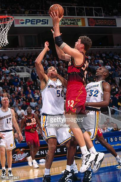 Christian Laettner of the Atlanta Hawks shoots against Joe Smith of the Golden State Warriorson February 4 1997 at San Jose Arena in San Jose...