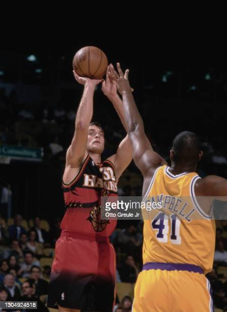 Christian Laettner, Power Forward and Center for the Atlanta Hawks prepares to make a jump shot as Elden Campbell of the Los Angeles Lakers reaches...
