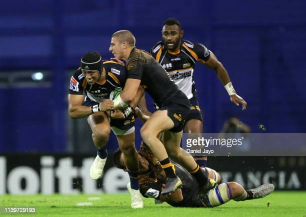 Christian Lealiifano of Brumbies is tackled by Sebastian Cancelliere of Jaguares during a Super Rugby Rd 11 match between Jaguares and Brumbies at...