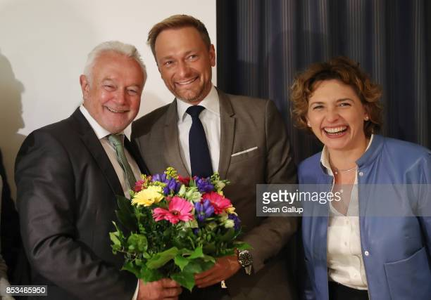 Christian Lindner head of the ree Democratic Party smiles after having recieved flowers from leading FDP member Wolfgang Kubicki as Nicola Beer looks...