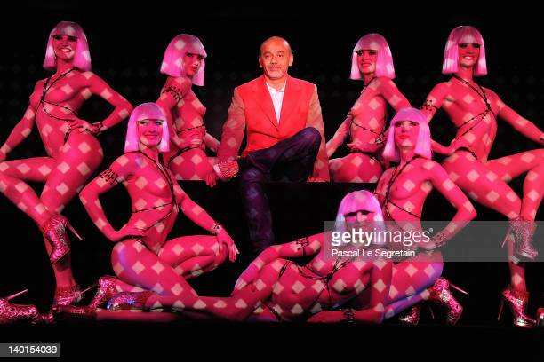 Christian Louboutin poses with Crazy Horse dancers after a performance of 'Feu' by Christian Louboutin at Le Crazy Horse on February 29 2012 in Paris...
