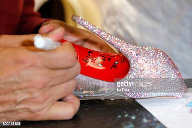 Christian Louboutin signs shoes during the Christian Louboutin Store Opening on June 23 2017 in Munich Germany