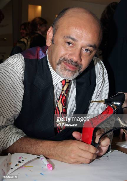 Christian Louboutin signs shoes for customers at Barneys New York on May 1 2008 in New York City