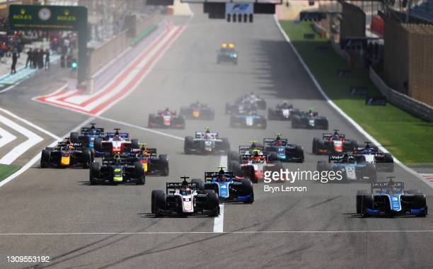 Christian Lundgaard of Denmark and ART Grand Prix and Guanyu Zhou of China and UNI-Virtuosi Racing battle for position into turn one at the start...