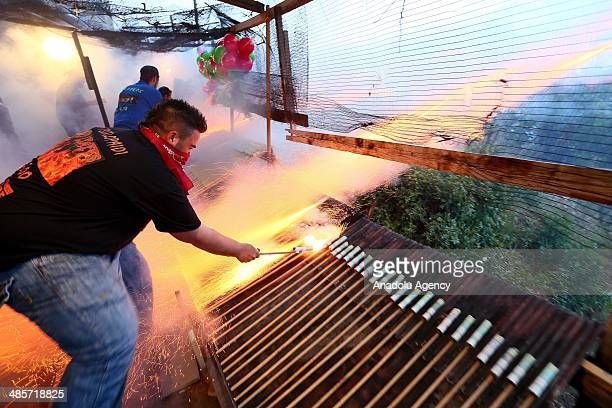 Christian man ignites home-made rockets at 'Rocket War' during Greek Orthodox Easter celebrations in the town of Vrontados on the Greek island of...