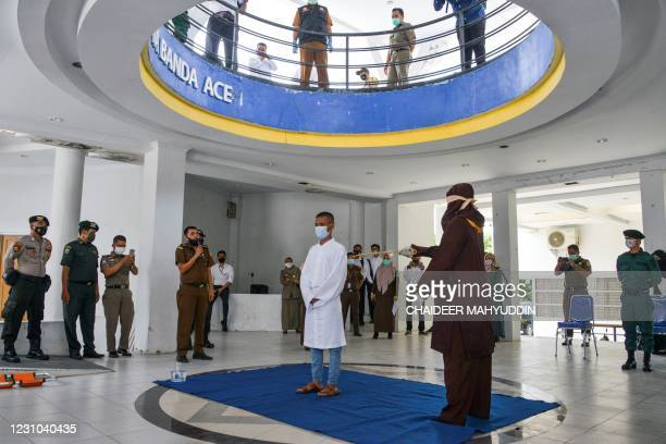 Christian man react while publicly caned by a member of the Sharia police after he was caught gambling in Banda Aceh on February 8, 2021.