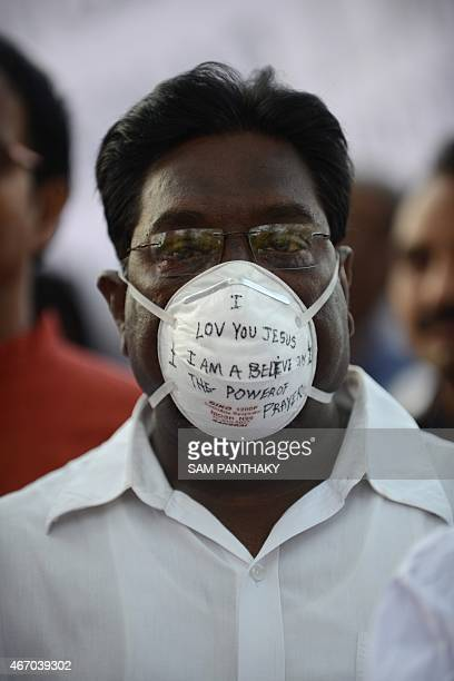 A Christian man wearing a protective face mask as a precaution against the swine flu attends a peace protest in Ahmedabad on March 20 in the wake of...
