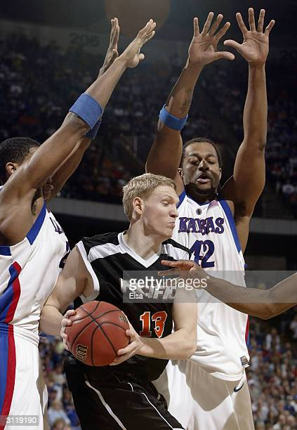 Christian Maraker of the Pacific Tigers is shut down by Jeff Graves and Wayne Simien of the Kansas Jayhawks during the second round game of the NCAA...