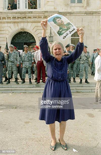 Christian Maronite east Beirut elderly woman shouts while brandishing portrait of Christian General Michel Aoun 06 November 1989 in the front of the...