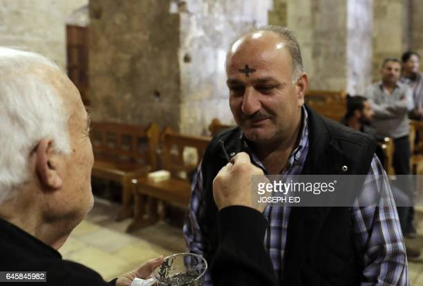 A Christian Maronite priest marks a cross with ash on the forehead of a Lebanese man at a church in the coastal city of Byblos north of Beirut on...