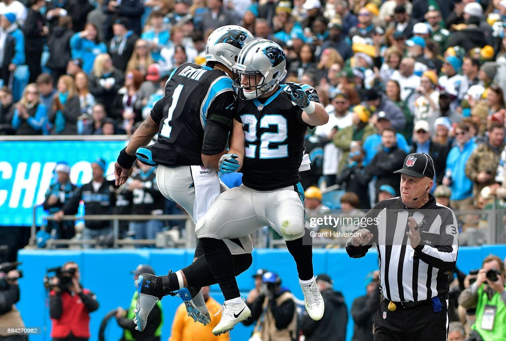 Christian McCaffrey #22 celebrates with teammate Cam Newton #1 of the Carolina Panthers after a touchdown against the Green Bay Packers in the first quarter during their game at Bank of America Stadium on December 17, 2017 in Charlotte, North Carolina.