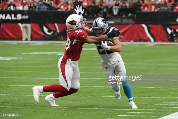 Christian McCaffrey of the Carolina Panthers attempts to run through a tackle by Jordan Hicks of the Arizona Cardinals during the first half at State...