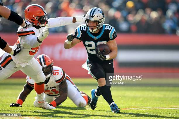 Christian McCaffrey of the Carolina Panthers carries the ball in front of the defense of Emmanuel Ogbah of the Cleveland Browns during the first...