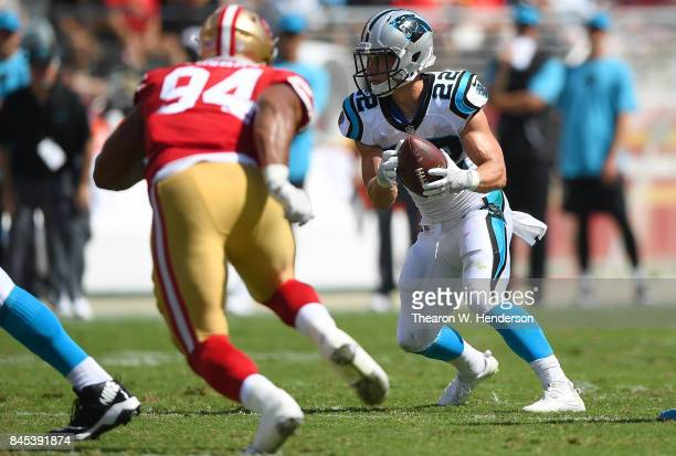 Christian McCaffrey of the Carolina Panthers carries the ball while pursued by Solomon Thomas of the San Francisco 49ers during the second quarter of...