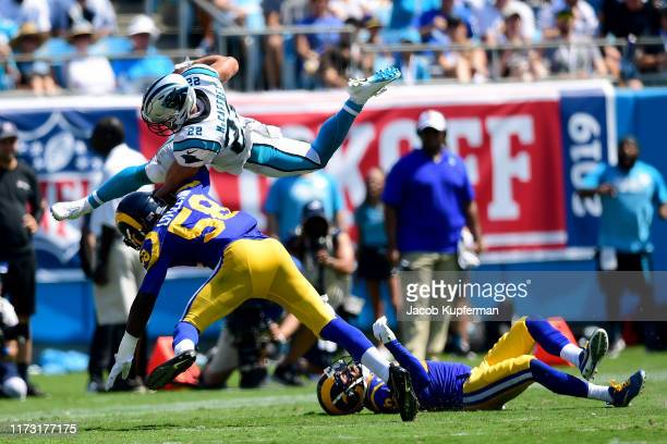 Christian McCaffrey of the Carolina Panthers hurdles over Eric Weddle of the Los Angeles Rams and is brought down by Cory Littleton of the Los...