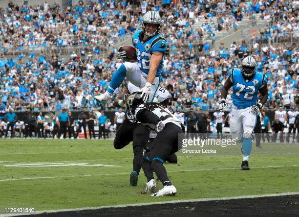 Christian McCaffrey of the Carolina Panthers jumps over Tre Herndon of the Jacksonville Jaguars for a touchdown during their game at Bank of America...