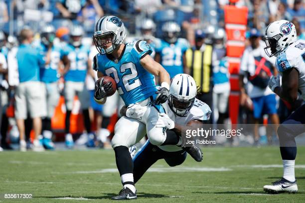 Christian McCaffrey of the Carolina Panthers runs through a tackle attempt by Denzel Johnson of the Tennessee Titans in the second quarter of a...
