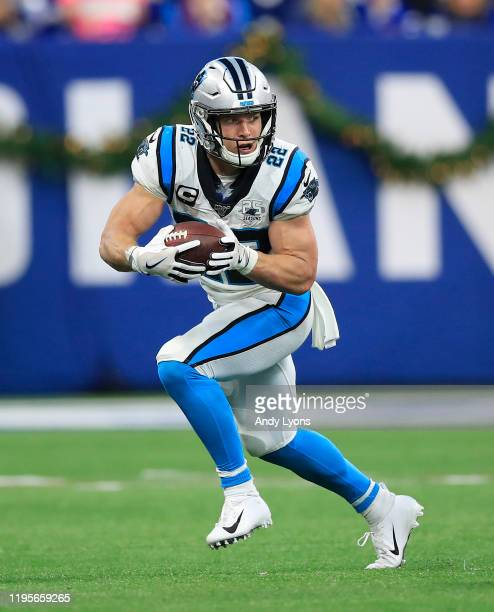 Christian McCaffrey of the Carolina Panthers runs with the ball while defended by Clayton Geathers of the Indianapolis Colts at Lucas Oil Stadium on...