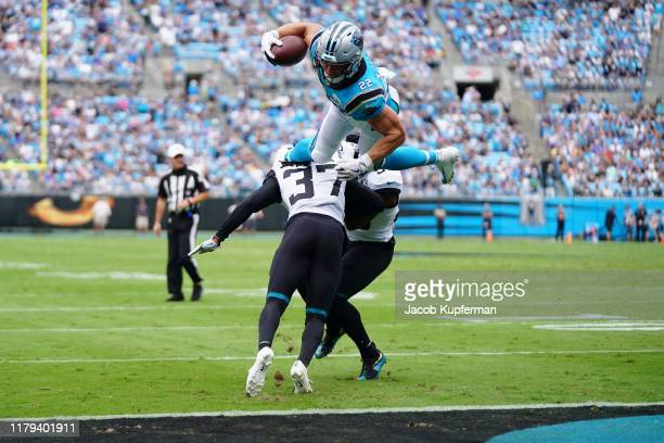 Christian McCaffrey of the Carolina Panthers scores a touchdown by leaping over Tre Herndon of the Jacksonville Jaguars in the first quarter during...