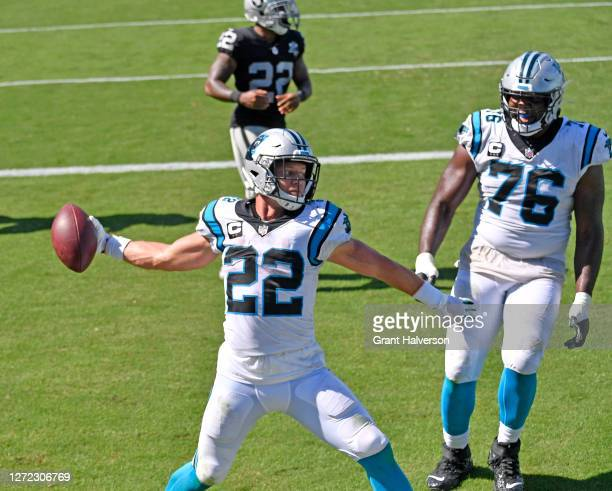Christian McCaffrey of the Carolina Panthers spikes the ball after scoring a touchdown against the Las Vegas Raiders during the fourth quarter at...