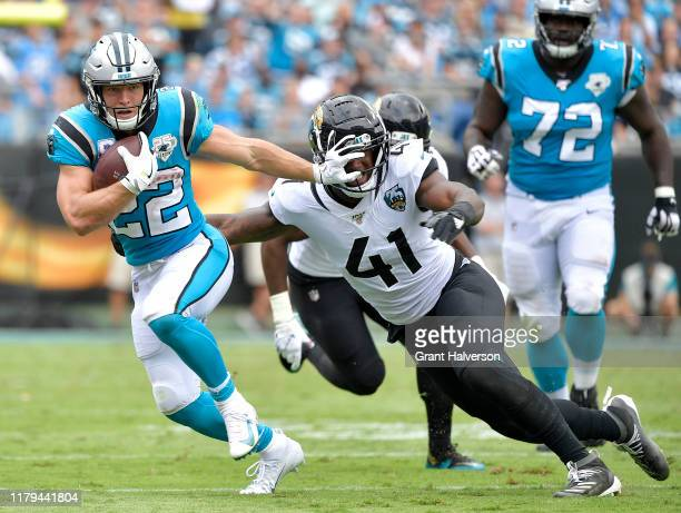 Christian McCaffrey of the Carolina Panthers stiff-arms Josh Allen of the Jacksonville Jaguars during the second half of their game at Bank of...