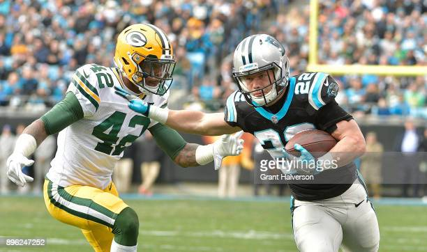 Christian McCaffrey of the Carolina Panthers stiffarms Morgan Burnett of the Green Bay Packers during their game at Bank of America Stadium on...