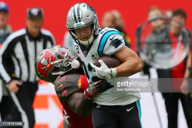 Christian McCaffrey of the Panthers stiff arms Devin White of the Bucs as McCaffrey runs for a touchdown during the game between the Carolina...