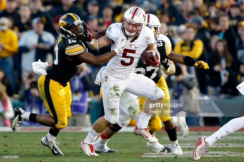 Christian McCaffrey #5 of the Stanford Cardinal runs past Joshua Jackson #15 and Jordan Lomax #27 of the Iowa Hawkeyes in the second half of the 102nd Rose Bowl Game on January 1, 2016 at the Rose Bowl in Pasadena, California.
