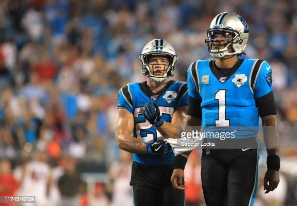 Christian McCaffrey wipes his hands on the towel of teammate Cam Newton of the Carolina Panthers during their game against the Tampa Bay Buccaneers...