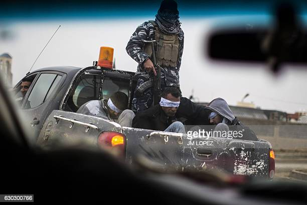 Christian militia fighters from the Nineveh Plain Protection Units drive a pick-up truck in Qaraqosh , transporting four men, allegedly members of...