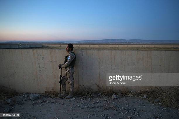 Christian militiaman looks towards the sunset in the abandoned streets of Telskuf on November 4, 2015 near the frontline with ISIS fighters in...