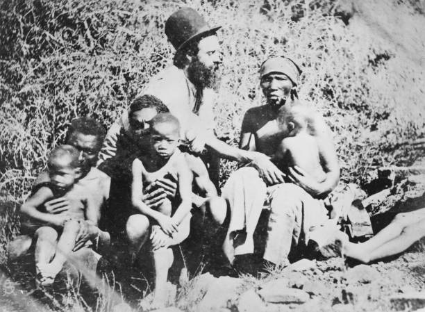 A Christian missionary with a group of Africans in...