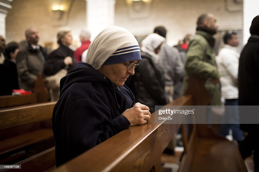 A Christian nun prays during the Christmas mass at the Church of the Nativity on December 25, 2013 in Bethlehem, West Bank. Every Christmas pilgrims travel to the church where a gold star embedded in the floor marks the spot where Jesus was believed to have been born.