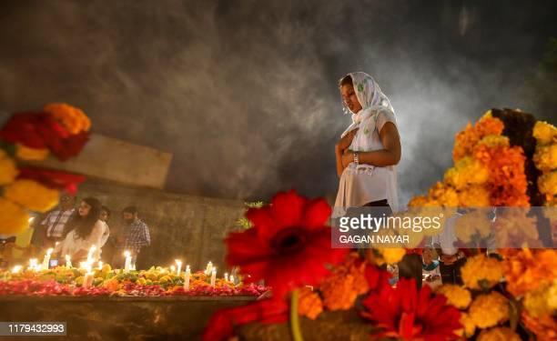 Christian offers prayers after lighting candles on the grave of departed ones during the celebrations of All Souls Day in a cemetery in Bhopal on...