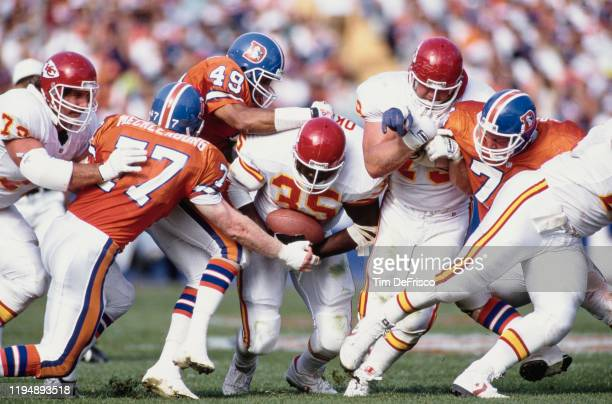 Christian Okoye Running Back for the Kansas City Chiefs is tackled running the ball by Karl Mecklenburg and Dennis Smith of the Denver Broncos during...