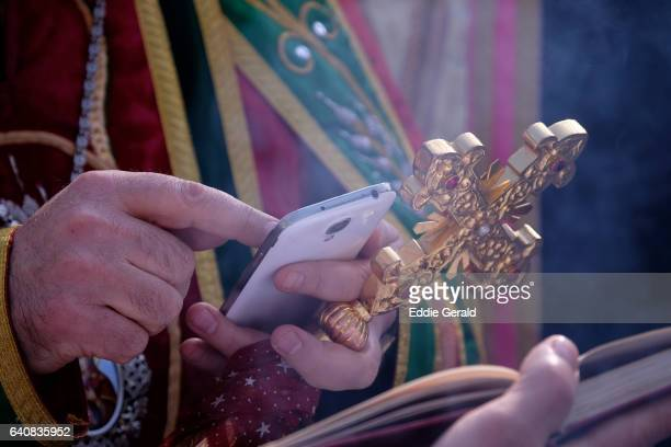 A Christian Orthodox cleric using a smart phone as he leads a religious procession