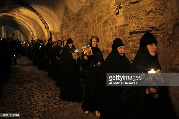 Christian Orthodox nuns holding candles and flowers walk on August 25 2015 through Jerusalem's Old City in a religious procession marking The...