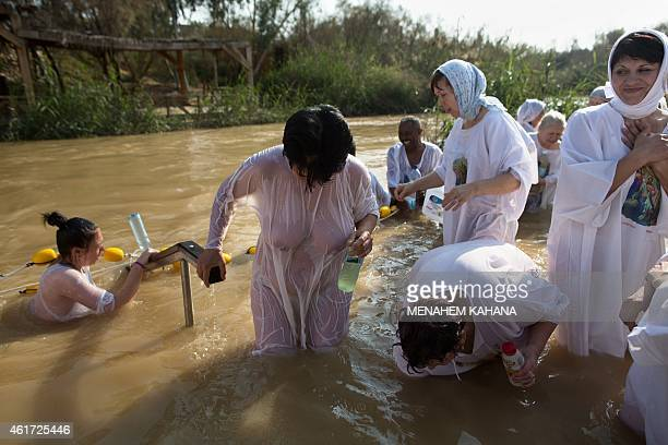 Christian Orthodox pilgrims immerse themselves into the waters of the Jordan River during a baptism ceremony as part of the Orthodox Feast of the...