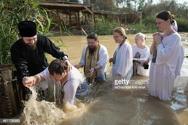 Christian Orthodox priests baptize a pilgrim into the waters of the Jordan River during a baptism ceremony as part of the Orthodox Feast of the...