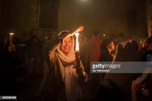 Christian Orthodox worshipers hold candles lit from a flame that emerged from the tomb believed to be of Jesus Christ as they take part in the...