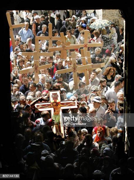 Christian Orthodox worshippers carry wooden crosses into the Church of the Holy Sepulchre during the Good Friday procession in Jerusalem's Old City...