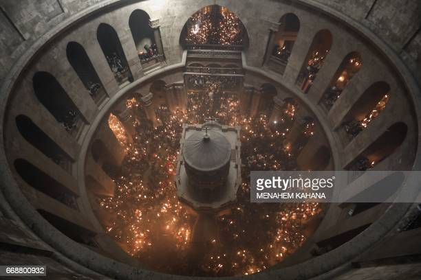 Christian Orthodox worshippers hold candles during the ceremony of the Holy Fire as thousands gather in the Church of the Holy Sepulchre in...