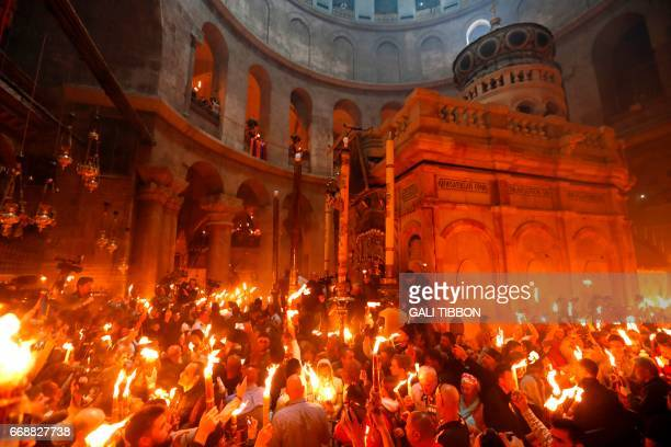 Christian Orthodox worshippers hold candles during the ceremony of the 'Holy Fire' as thousands gather in the Church of the Holy Sepulchre in...