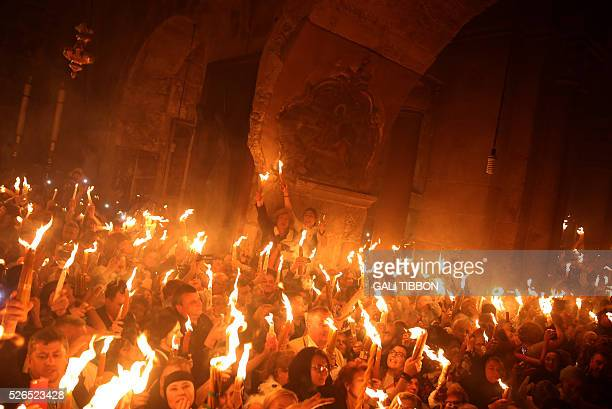 TOPSHOT Christian Orthodox worshippers hold candles lit from the Holy Fire as thousands gather in the Church of the Holy Sepulchre in Jerusalem's Old...