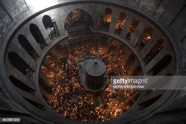 TOPSHOT Christian Orthodox worshippers hold up candles during the ceremony of the Holy Fire as they gather in the Church of the Holy Sepulchre in...