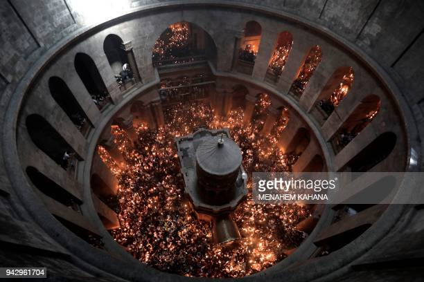 "Christian Orthodox worshippers hold up candles during the ceremony of the ""Holy Fire"" as they gather in the Church of the Holy Sepulchre in..."