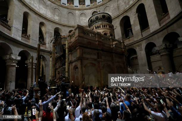 Christian Orthodox worshippers hold up candles lit from the Holy Fire as they gather in the Church of the Holy Sepulchre in Jerusalems Old City on...