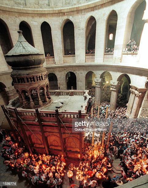 Christian Orthodox worshippers pass the Holy Fire to fellow worshippers around the tomb of Christ in the Church of the Holy Sepulcher May 4 2002 in...