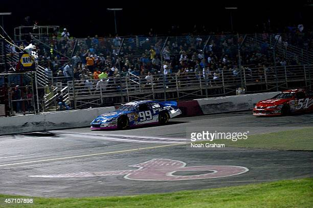 Christian PaHud driver of the PEAK Toyota drives across the finish line in first place during the NASCAR KN Toyota/NAPA Auto Parts 150 at the All...